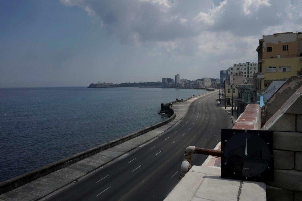 Набережная Малекона изображена рядом с почти пустой дорогой в полдень в Гаване, Куба