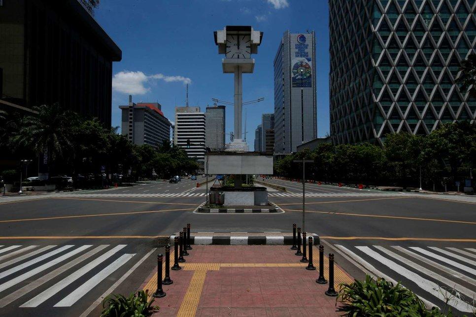 В полдень на Джалане М.Х. Тамрин, на одной из главных дорог Джакарты, Индонезия, виден практически пустой перекресток с низкой интенсивностью движения
