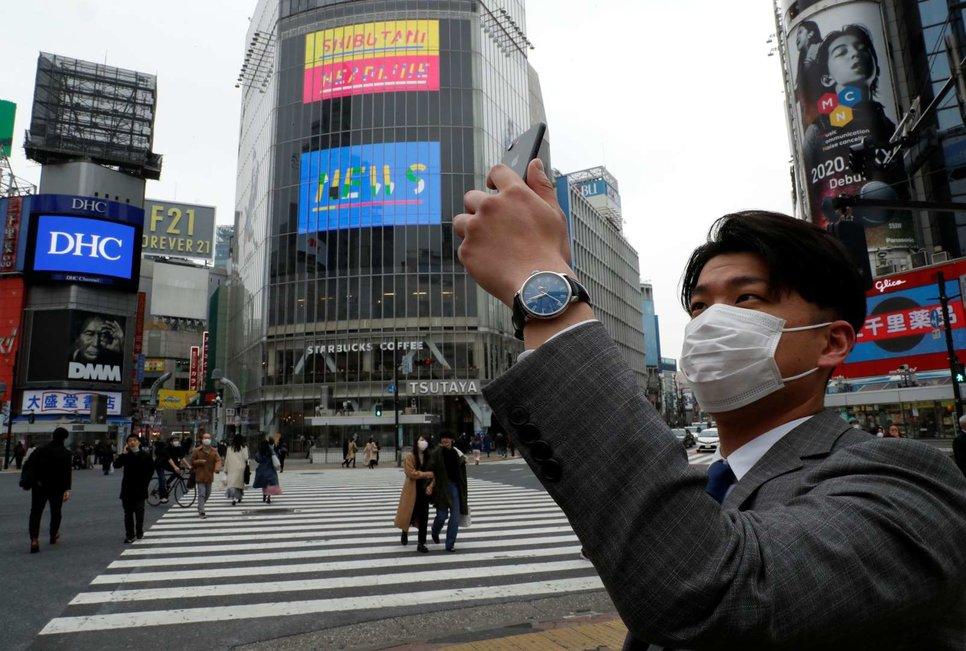 Человек в защитной маске делает снимок своим мобильным телефоном в полдень на перекрестке Сибуя в Токио, Япония